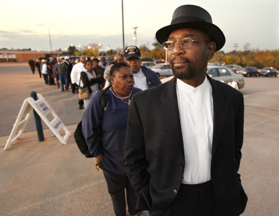 Photo - Roosevelt Milton, president of the Oklahoma City Chapter of the NAACP, stands in line with voters as the sun rises while waiting for precinct 551 to open to vote at Millwood High School in Oklahoma City Tuesday, Nov. 4, 2008. BY PAUL B. SOUTHERLAND, THE OKLAHOMAN