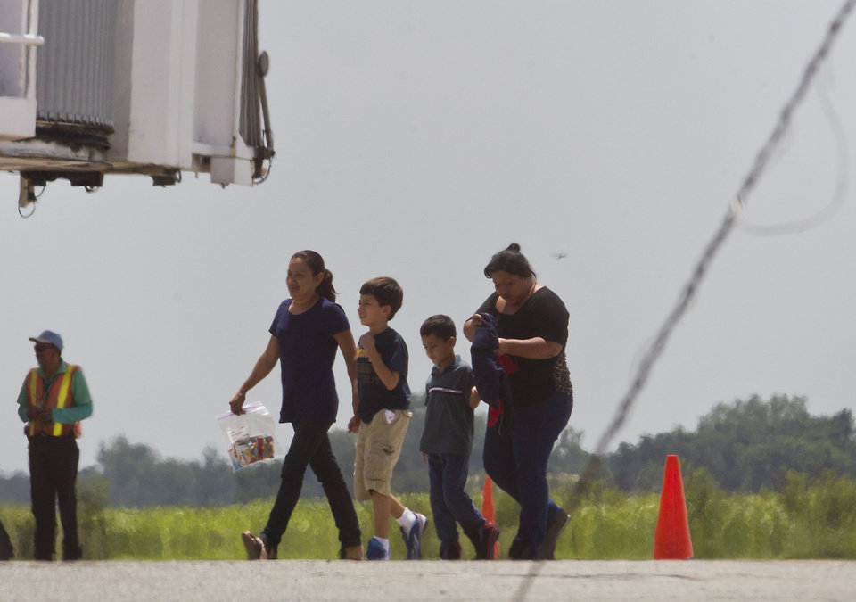 Photo - Two women and their children, who were deported from the United States, walk on the tarmac after deplaning at the San Pedro Sula airport, in Honduras, Friday, July 18, 2014. (AP Photo/Esteban Felix)