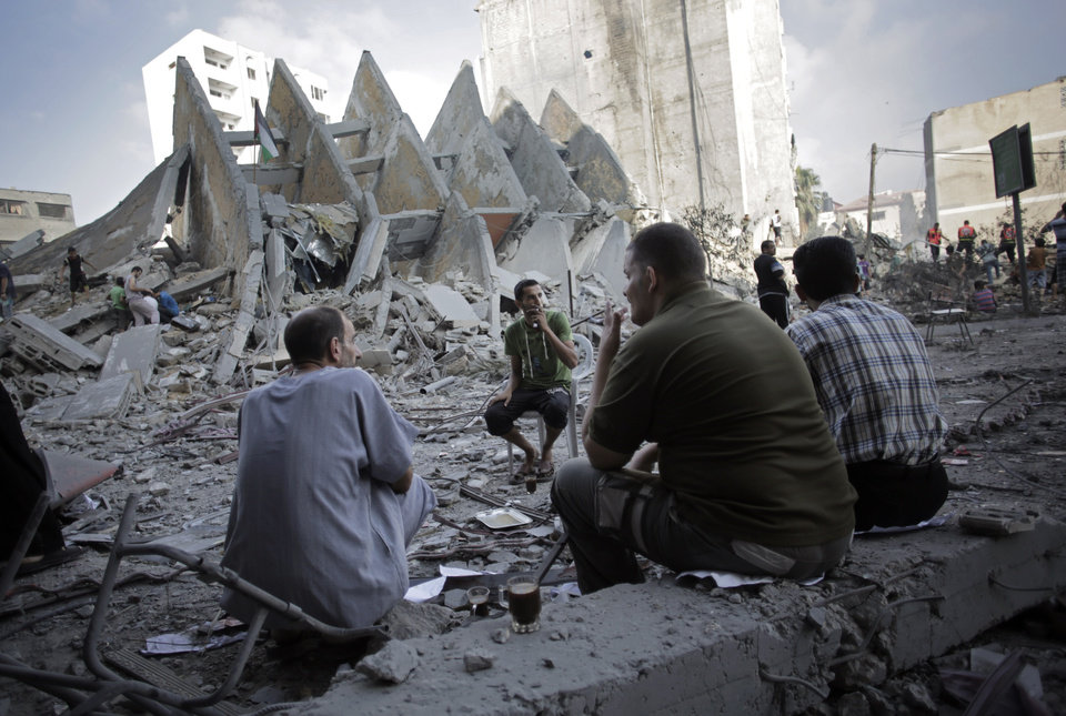 Photo - Palestinians have a coffee next to the rubble of the 15-story Basha Tower that collapsed from early morning Israeli airstrikes in Gaza City, Tuesday, Aug. 26, 2014. Tuesday's strikes leveled the Basha Tower with apartments and offices and severely damaged another high-rise, the Italian Complex, built in the 1990s by an Italian businessman, with dozens of shops and offices. Both buildings were evacuated after receiving warnings of impending strikes. (AP Photo/Khalil Hamra)