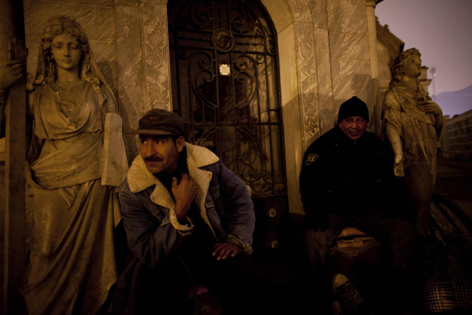 In this Nov.10, 2012 photo, private security guards watch visitors take a nighttime guided tour through the Presbitero Matias Maestro cemetery in Lima, Peru. The cemetery, created by one of the last Spanish viceroys, was established the outside the walls of old Lima. (AP Photo/Rodrigo Abd)
