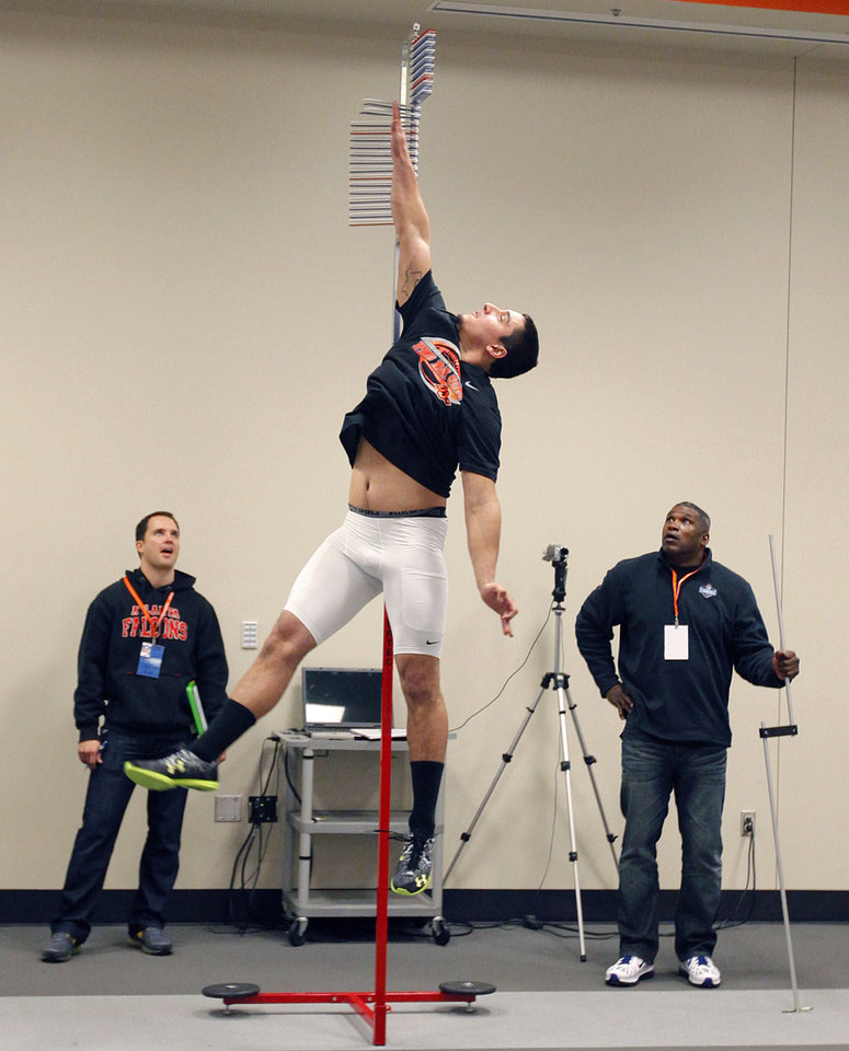 Photo - Scouts look on as Justin Gent gets a measurement on his vertical jump during the NFL pro day at Oklahoma State University on Wednesday, March 9, 2011, in Stillwater, Okla.  Photo by Chris Landsberger, The Oklahoman