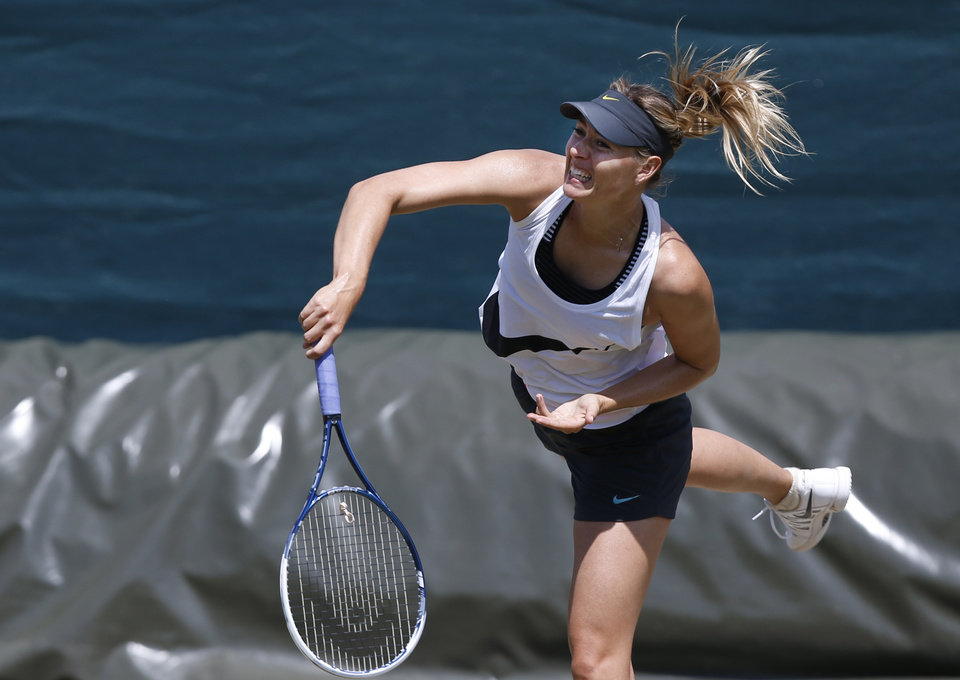 Photo - Maria Sharapova of Russia plays a shot during a practice session ahead of the All England Lawn Tennis Championships in Wimbledon, London,  Sunday June  22, 2014. The Championships start Monday June 23. (AP Photo/Sang Tan)