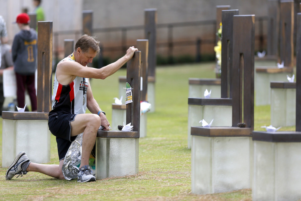Photo - Roger Jacobi places his bib on the chair of Ashley Megan Eckles at the Oklahoma City National Memorial after running the half marathon in the Oklahoma City Memorial Marathon in Oklahoma City, Sunday, April 28, 2019. [Bryan Terry/The Oklahoman]