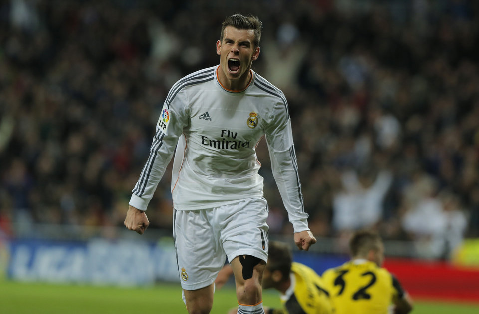 Photo - Real's Gareth Bale celebrates after scoring during a Spanish La Liga soccer match between Real Madrid and Sevilla at the Santiago Bernabeu stadium in Madrid, Spain, Wednesday Oct. 30, 2013. (AP Photo/Andres Kudacki)