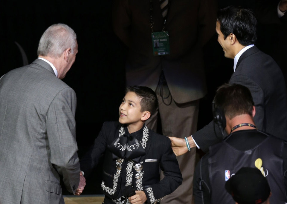 Photo - Sebastien De la Cruz is greeted by San Antonio Spurs' Gregg Popovich, left, and Miami Heat's Erik Spoelstra after singing the national anthem before Game 4 of the NBA Finals basketball series, Thursday, June 13, 2013, in San Antonio. (AP Photo/David J. Phillip)