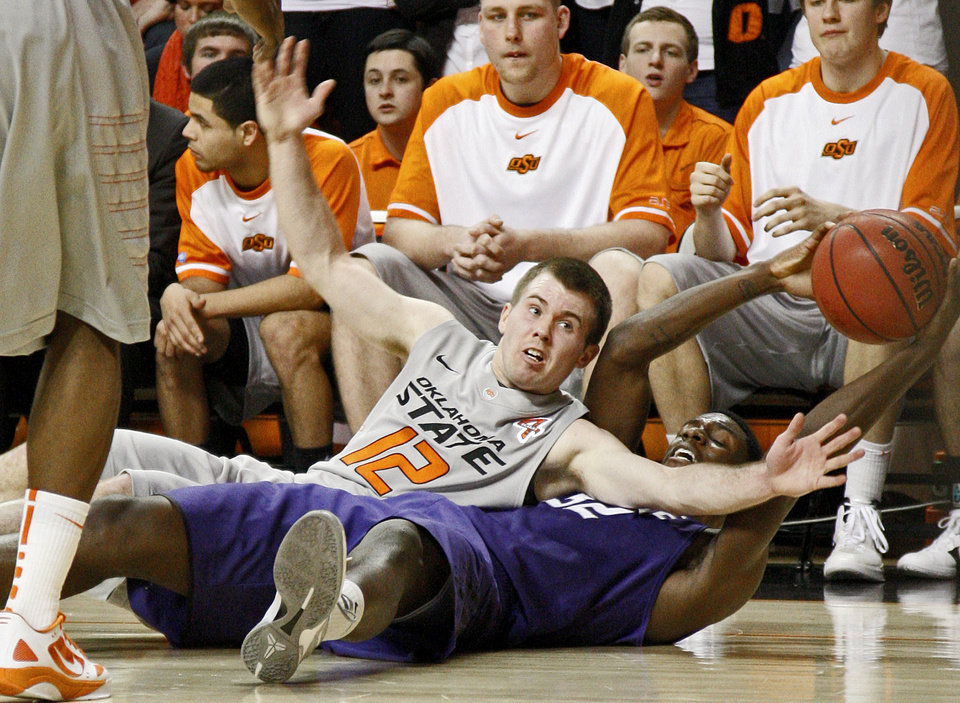 Photo - Kansas State's Jamar Samuels (32) looks to pass around Oklahoma State's Keiton Page (12) during an NCAA college basketball game between the Oklahoma State University Cowboys (OSU) and the Kansas State University Wildcats (KSU) at Gallagher-Iba Arena in Stillwater, Okla., Saturday, Jan. 21, 2012. Photo by Bryan Terry, The Oklahoman