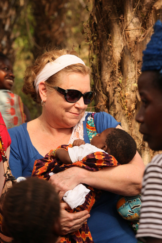 Photo - During a recent Water4 mission trip, gospel recording artist Sandi Patty bonds with an infant in a large village about two hours outside of Ronurie in Sierra Leone.