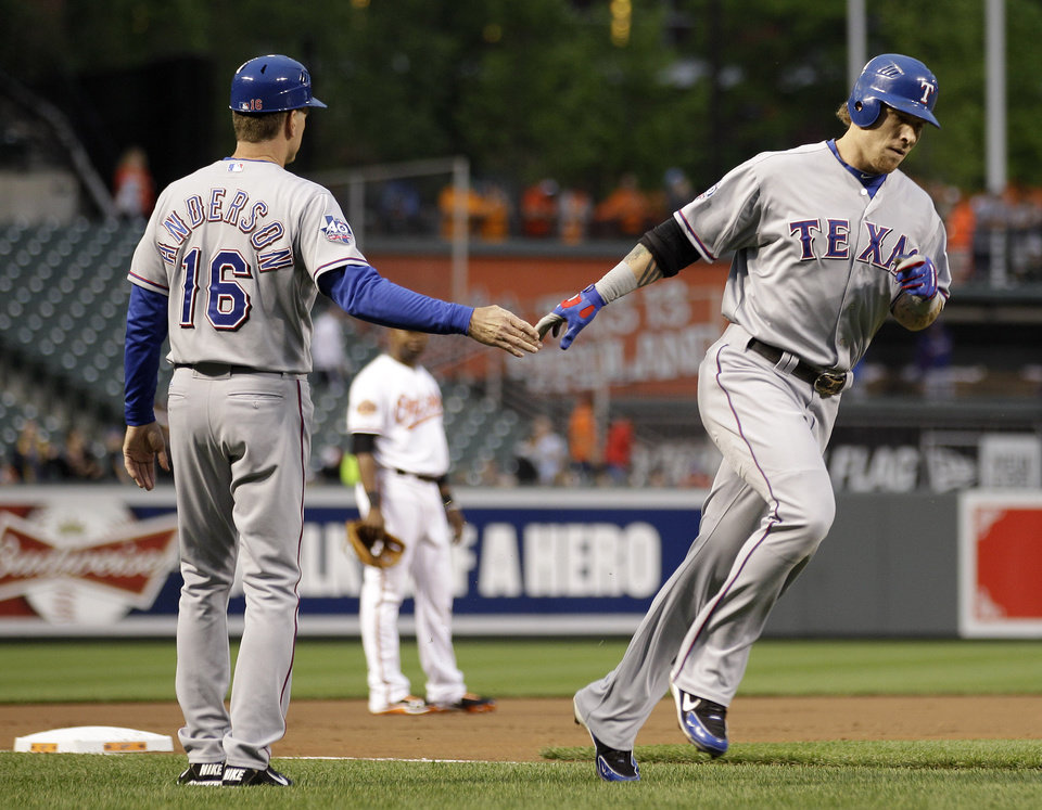 Photo -   Texas Rangers' Josh Hamilton, right, high-fives third base coach Dave Anderson as he rounds the bases after hitting a two-run home run in the first inning of a baseball game against the Baltimore Orioles in Baltimore, Tuesday, May 8, 2012. (AP Photo/Patrick Semansky)