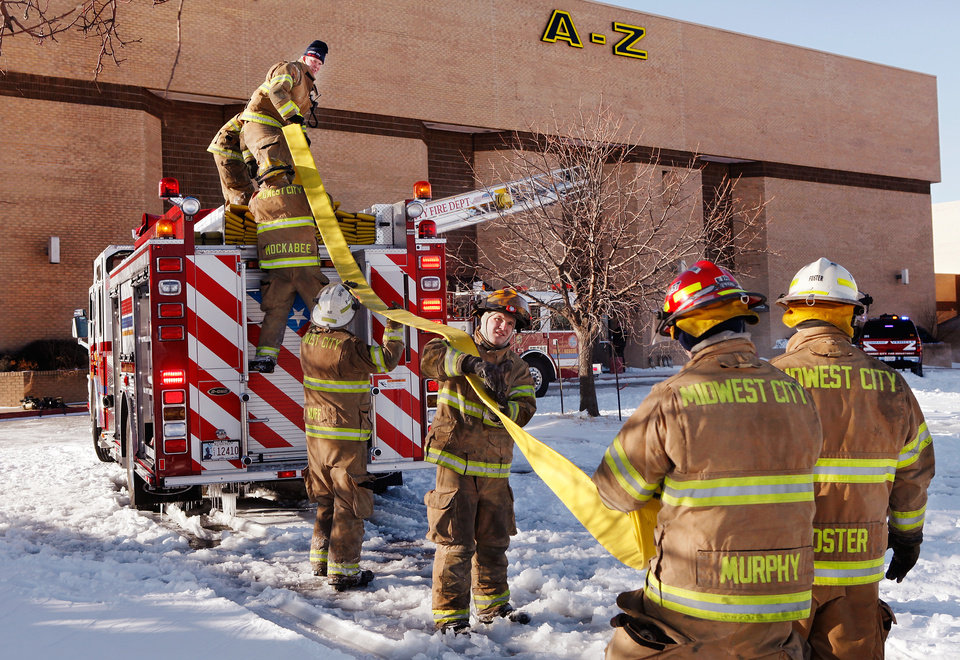 Photo -  It took several firefighters working together to roll this hose, made stiff by single digit temperatures, and load it back onto their firetruck after they put out a fire  in a vacant mall near Reno and Air Depot in Midwest City, Thursday morning, Feb. 3, 2011.  Someone set a fire inside a former store called A - Z, said Midwest City Fire Marshal Jerry Lojka.