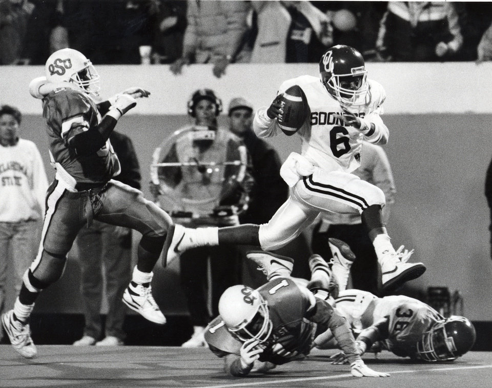 Photo - OU's Charles Thompson leaps over OSU's Mike Clark on his way to the winning touchdown in the fourth quarter of the Bedlam college football game on Nov. 5, 1988. Staff photo by David McDaniel