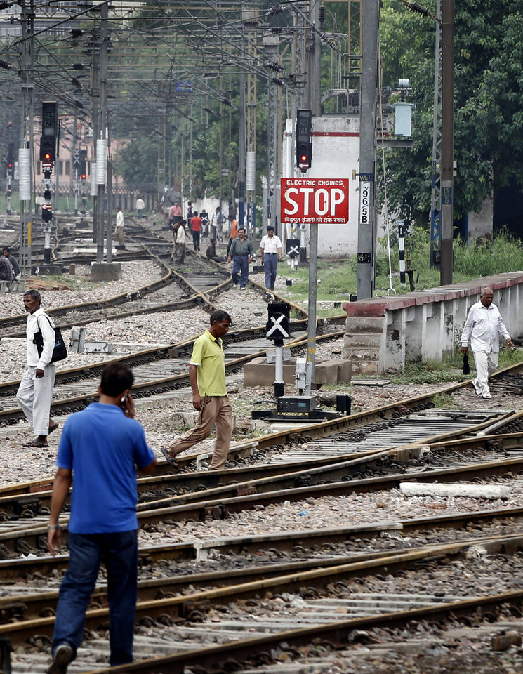 Photo -   Commuters walk on empty railway tracks at the New Delhi railway station following a power outage in New Delhi, India, Tuesday, July 31, 2012. India's energy crisis cascaded over half the country Tuesday when three of its regional grids collapsed, leaving more than 600 million people without government-supplied electricity in one of the world's biggest-ever blackouts. (AP Photo/Mustafa Quraishi)