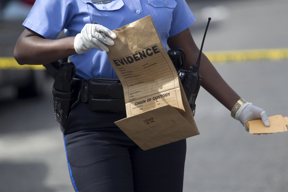 Photo - New Orleans police officer collects evidence at the scene of a shooting at the intersection Frenchman Street at N. Villere on Mother's Day in New Orleans, Sunday May 12, 2013. Gunmen opened fire on dozens of people marching in a Mother's Day neighborhood parade in New Orleans on Sunday, wounding at least 17, police said. (AP Photo/Doug Parker)