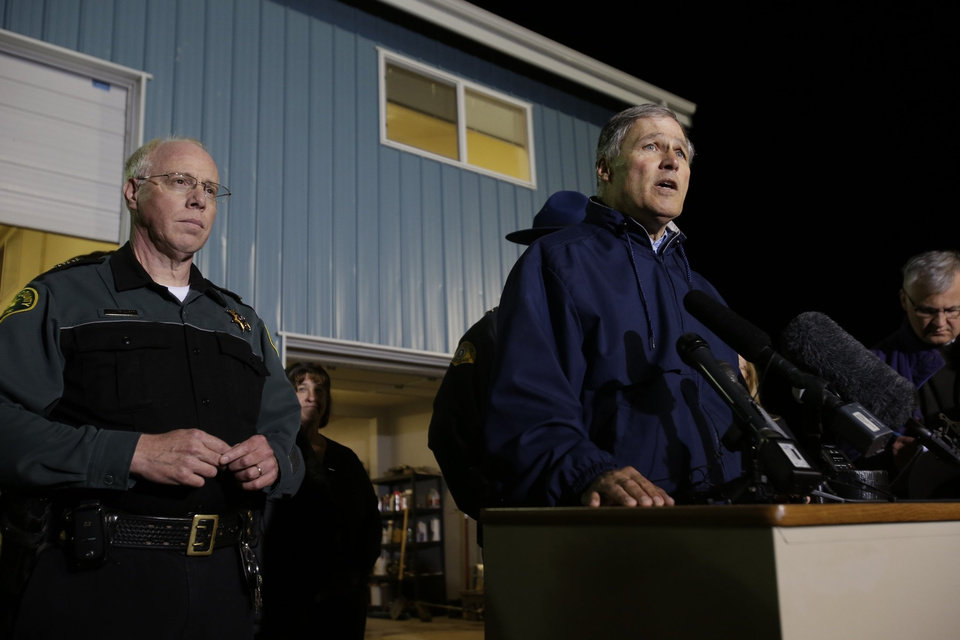 Photo - Washington Governor Jay Inslee, right, talks to reporters about the failure of the Interstate highway bridge crossing the Skagit River in Mt. Vernon Thursday May 23, 2013, dumping two vehicles into the water and sparking a rescue effort by boats and divers as three injured people were pulled from the chilly waterway. Early reports indicate this semi trailier may have struck the bridge. (AP Photo/Seattle Times, Dean Rutz) OUTS: SEATTLE OUT, USA TODAY OUT, MAGAZINES OUT, TELEVISION OUT, SALES OUT. MANDATORY CREDIT TO:  DEAN RUTZ / THE SEATTLE TIMES.