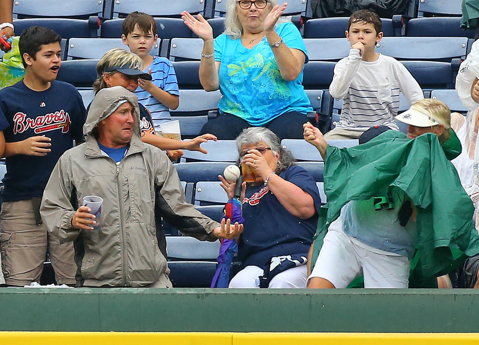 Photo - Atlanta Braves fans react to the ball coming into the stands on a two run home run by Chris Johnson during the second inning of a baseball game against the Philadelphia Phillies on Sunday, July 20, 2014, in Atlanta. (AP Photo/Atlanta Journal-Constitution, Curtis Compton)