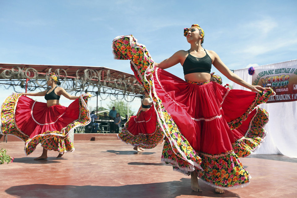Photo - FILE - In this May 5, 2016, file photo, Minerva Allende, right, dances with her fellow dancers of Cuerpo Escena Comania de Danza from the Institute of Chihuahua in celebration of Cinco de Mayo at the LULAC/Hispanic Heritage of Odessa's annual Fiesta Lunch at the La Margarita Festival Grounds in Odessa, Texas. Trump's immigration policies and rhetoric are leaving some Mexican Americans and immigrants feeling at odds with a day they already thought was appropriated by beer and liquor companies, event promoters and local bars. (Jacob Ford/Odessa American via AP)