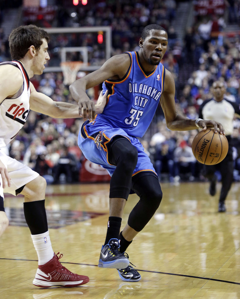 Oklahoma City Thunder forward Kevin Durant, right, dribbles against Portland Trail Blazers forward Victor Claver, from Spain, during the first quarter of an NBA basketball game in Portland, Ore., Friday, April 12, 2013. (AP Photo/Don Ryan) ORG XMIT: ORDR108
