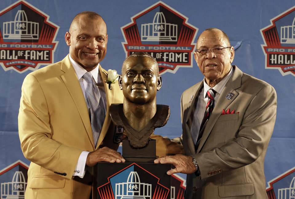 Photo - Hall of Fame inductee Aeneas Williams, left, poses with his presenter Lawrence Williams, his father, during the 2014 Pro Football Hall of Fame Enshrinement Ceremony at the Pro Football Hall of Fame Saturday, Aug. 2, 2014, in Canton, Ohio. (AP Photo/Tony Dejak)