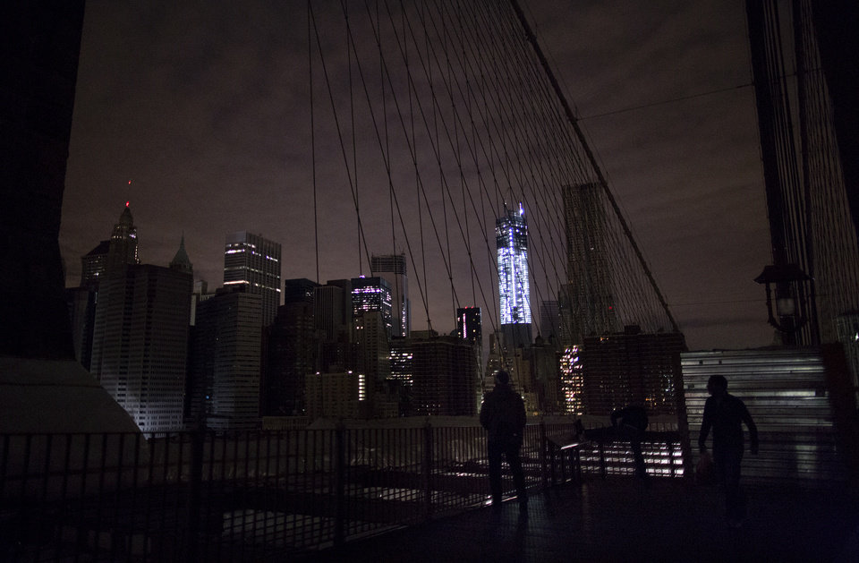 Photo - FILE - In this Nov. 1, 2012 file photo, much of lower Manhattan remains dark in the wake of Superstorm Sandy, as viewed from the darkened Manhattan side of the Brooklyn Bridge in New York. 2012 was a year of storms, of raging winds and rising waters, but also broader turbulence that strained our moorings. (AP Photo/Craig Ruttle, File)