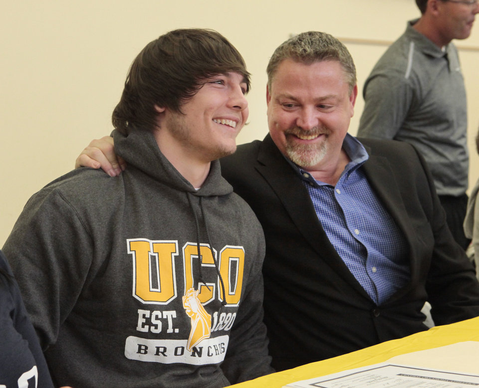 Eli Hooks signs a letter of intent with UCO, with his dad, Bryan,  during signing day at Deer Creek High School, Wednesday, February 4, 2014. Photo by David McDaniel, The Oklahoman