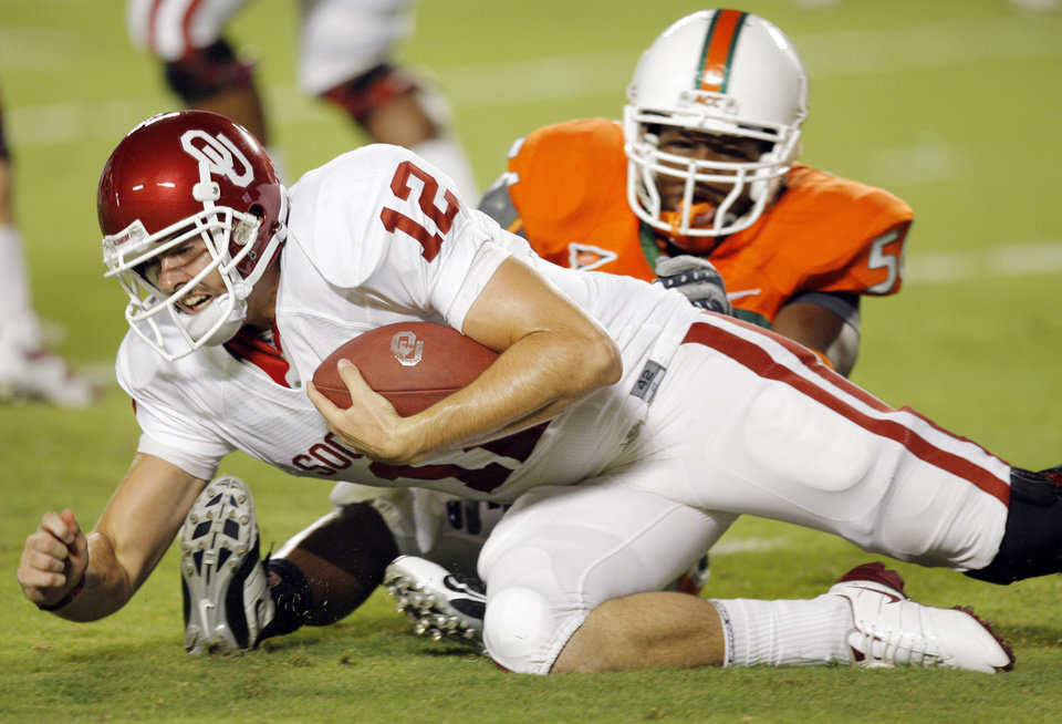 Photo - OU quarterback Landry Jones (12) is sacked by Miami's Marcus Robinson (56) during the college football game between the University of Oklahoma (OU) Sooners and the University of Miami (UM) Hurricanes at Land Shark Stadium in Miami Gardens, Florida, Saturday, October 3, 2009. Photo by Nate Billings, The Oklahoman