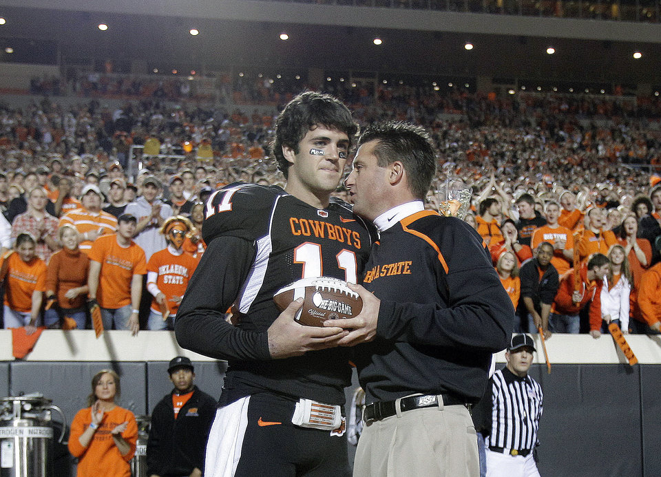 OSU head coach Mike Gundy greets quarterback Zac Robinson (11) as Robinson is recognized for senior night at the college football game between Oklahoma State University (OSU) and the University of Colorado (CU) at Boone Pickens Stadium in Stillwater, Okla., Thursday, Nov. 19, 2009. Photo by Sarah Phipps, The Oklahoman