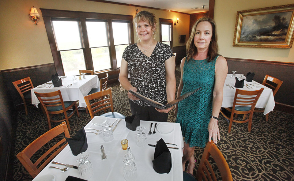 Photo -  Manager Kristi Jolly and owner Lisa Janes stand in a dining room at Twelve Oaks Restaurant. Twelve Oaks Restaurant was founded by Bill Horn, who moved an aging Victorian home in Guthrie to its current location south of the Lazy E Ranch. Photo by David McDaniel, The Oklahoman   David McDaniel -  The Oklahoman
