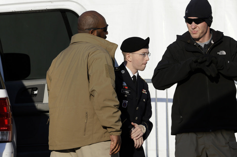 Photo - Army Pfc. Bradley Manning, second from right, steps out of a security vehicle as he is escorted into a courthouse in Fort Meade, Md., Thursday, Nov. 29, 2012, for a pretrial hearing. Manning is charged with aiding the enemy by causing hundreds of thousands of classified documents to be published on the secret-sharing website WikiLeaks. (AP Photo/Patrick Semansky)