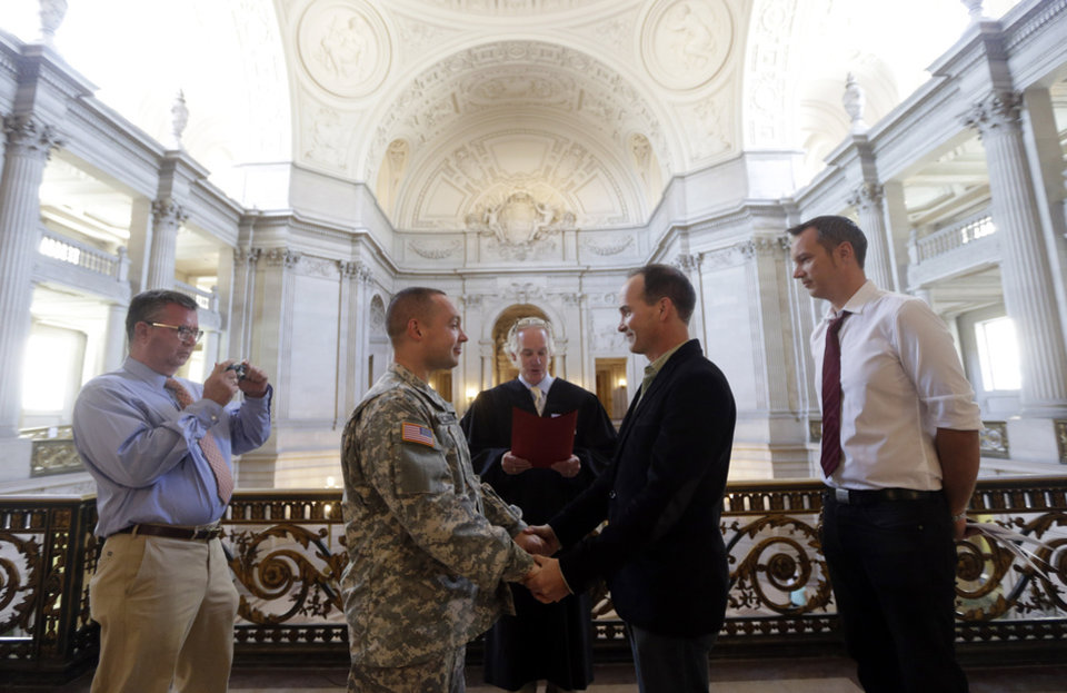 Photo - Army Capt. Michael Potoczniak,  center left, and Todd Saunders, of El Cerrito, Calif., are married by deputy marriage commissioner John Loschmann, center, as witnesses Bill Hershon, left, and Sean Boileau watch at City Hall in San Francisco, Saturday, June 29, 2013. Dozens of gay couples waited excitedly Saturday outside of San Francisco's City Hall as clerks resumed issuing same-sex marriage licenses, one day after a federal appeals court cleared the way for the state of California to immediately lift a 4 ½ year freeze. Big crowds were expected from across the state as long lines had already stretched down the lobby shortly after 9 a.m. City officials decided to hold weekend hours and let couples tie the knot as San Francisco is also celebrating its annual Pride weekend expected to draw as many as 1 million people. (AP Photo/Marcio Jose Sanchez)