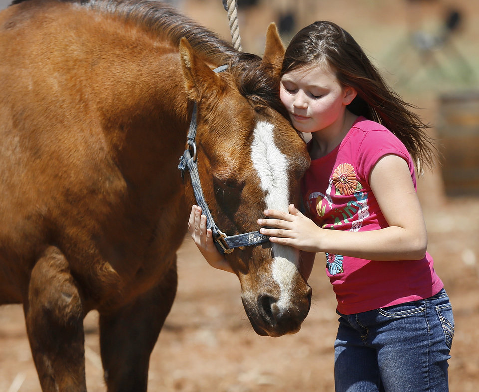 Photo -  Ryan Yingling, 10, of Oklahoma City, hugs Tommy, one of two horses available for children to see and touch at the Whistle-Stop and Festival in Wellston. Photo by Jim Beckel, The Oklahoman   Jim Beckel -