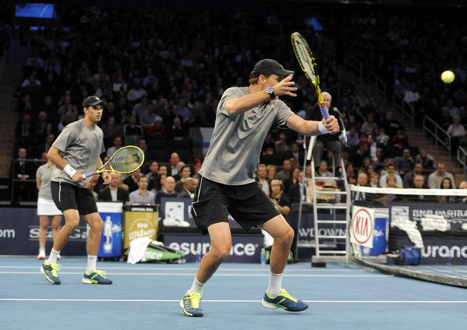 Photo - Mike Bryan, left, watches his brother, Bob return a shot against Patrick and John McEnroe in the BNP Paribas Showdown Tennis Tournament on Monday, March 3, 2014, in New York. The Bryans won 8-3. (AP Photo/Kathy Kmonicek)