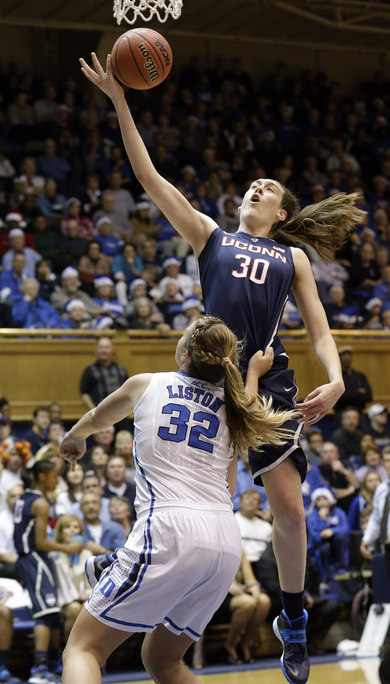 Photo - Connecticut's Breanna Stewart (30) drives to the basket as Duke's Tricia Liston (32) defends during the second half of an NCAA college basketball game in Durham, N.C., Tuesday, Dec. 17, 2013. Connecticut won 83-61.(AP Photo/Gerry Broome)