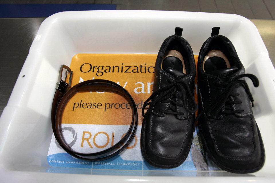 Photo - FILE - In this Wednesday, Jan. 10, 2007, file photo, a belt and shoes sit in a trays with advertising that is being used in the safety screening of travelers done by the Transportation Security Administration, at the Los Angeles International Airport in Los Angeles. The U.S Department of Homeland Security said Wednesday, Feb. 19, 2014, it is warning airlines that terrorists could try to hide explosives in shoes. It's the second time in less than three weeks that the government has issued a warning about possible attempts to smuggle explosives on a commercial jetliner. (AP Photo/Ann Johansson, File)