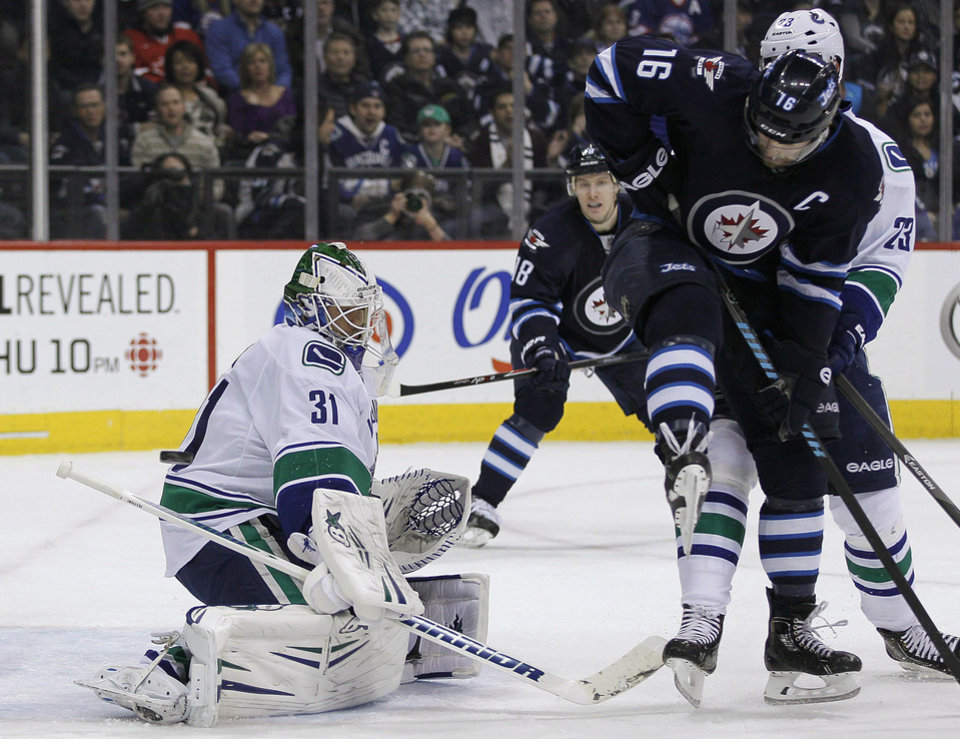 Photo - Vancouver Canucks goaltender Eddie Lack (31) saves the deflection by Winnipeg Jets' Andrew Ladd (16) during the second period of an NHL hockey game in Winnipeg, Manitoba, on Friday, Jan. 31, 2014. (AP Photo/The Canadian Press, John Woods)
