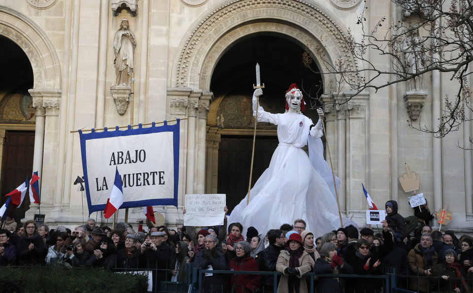 Photo - People demonstrate with a banner reading in Spanish