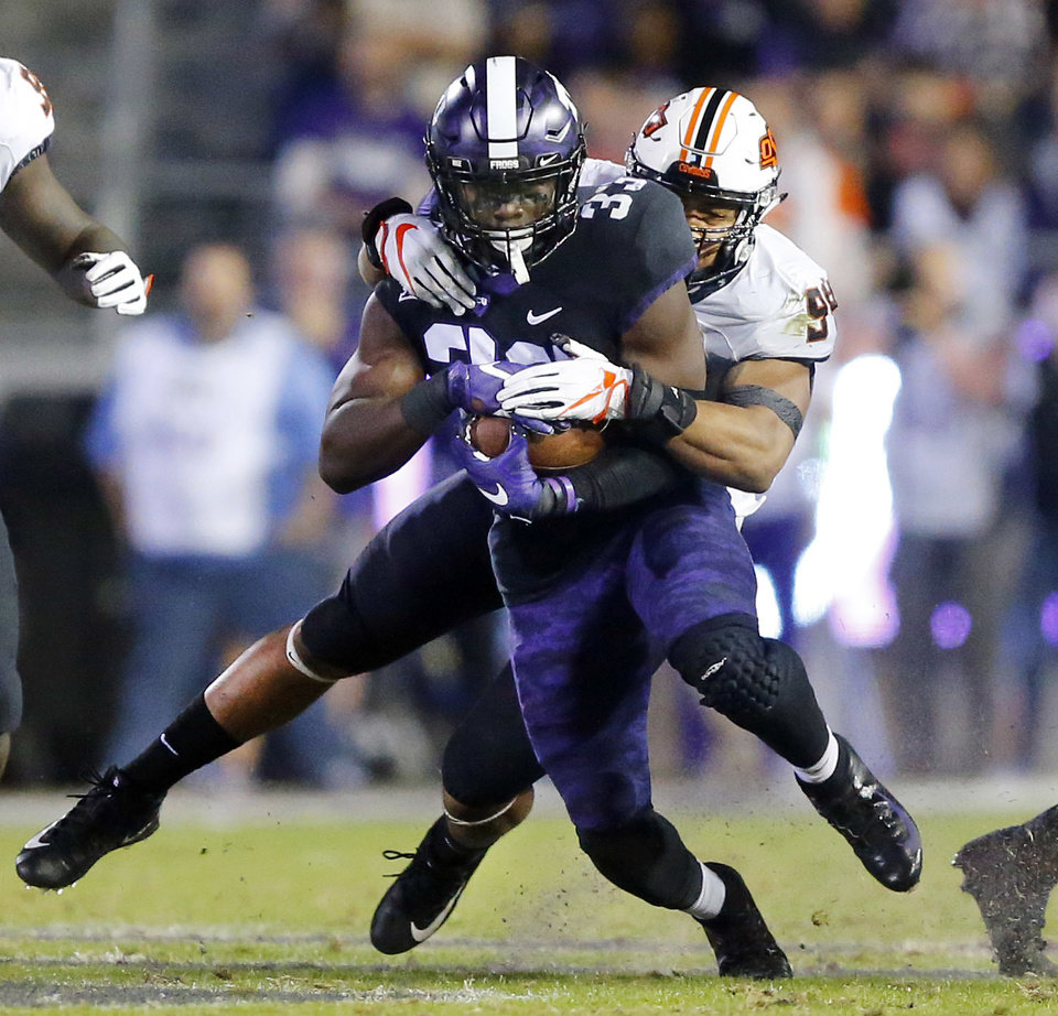 Photo -  Oklahoma State defensive end Jordan Brailford makes a diving tackle of TCU running back Sewo Olonilua during the second quarter of their game Saturday in Fort Worth, Texas. [PHOTO BY TOM FOX, The Dallas Morning News via AP]