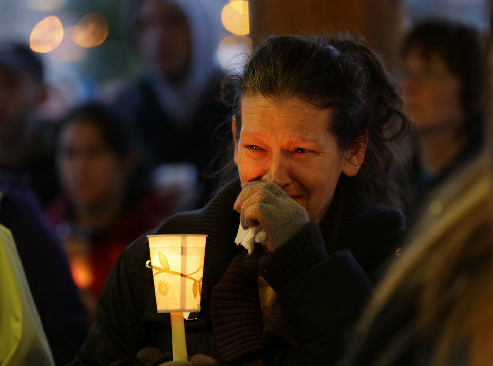 Photo - Teresa Welter cries as she holds a candle, Tuesday, March 25, 2014, at a candlelight vigil in Arlington, Wash., for the victims of a massive mudslide that struck the nearby community of Oso, Wash., on Saturday, killing at least 16 people and leaving dozens missing. (AP Photo/Ted S. Warren)