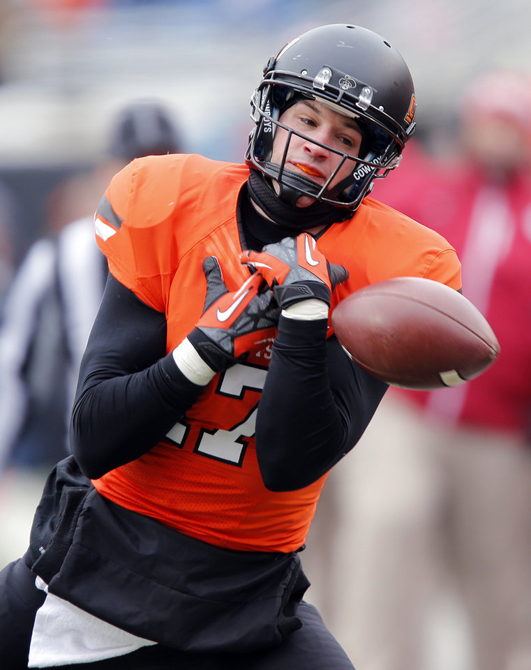 Photo - Oklahoma State's Charlie Moore (17) drops a pass during the Bedlam college football game between the Oklahoma State University Cowboys (OSU) and the University of Oklahoma Sooners (OU) at Boone Pickens Stadium in Stillwater, Okla., Saturday, Dec. 7, 2013. Photo by Chris Landsberger, The Oklahoman