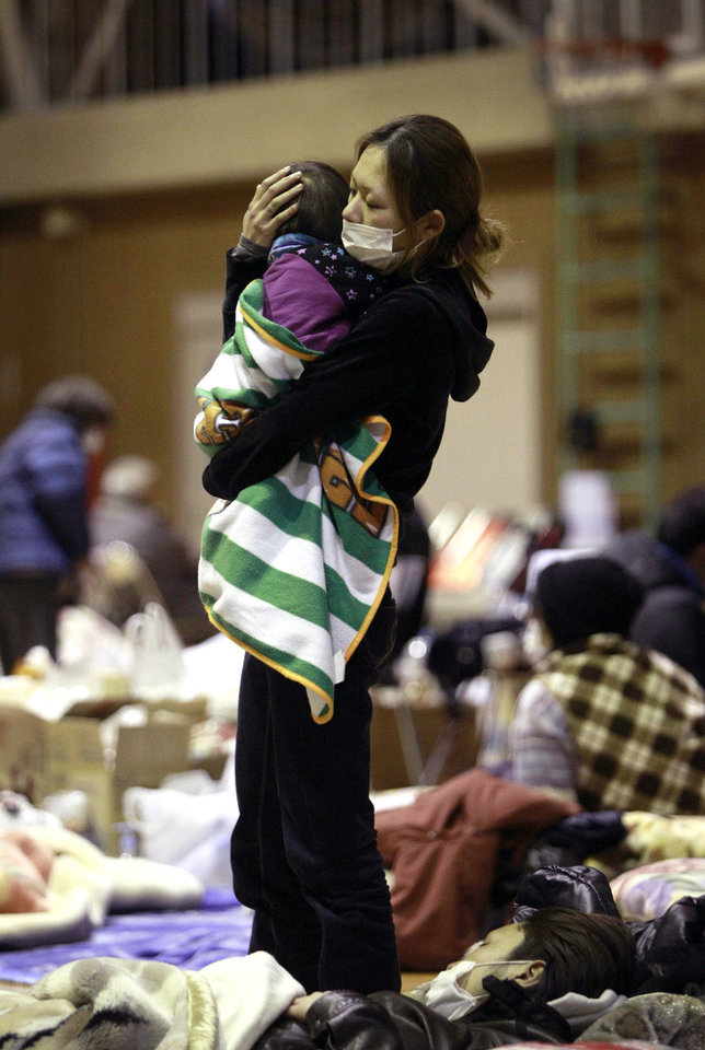 In this March 16, 2011, file photo, a woman holds her child at a shelter after being evacuated from areas around the Fukushima nuclear facilities in Fukushima city, Fukushima prefecture, Japan. AP file photo <strong>Wally Santana - AP file photo</strong>