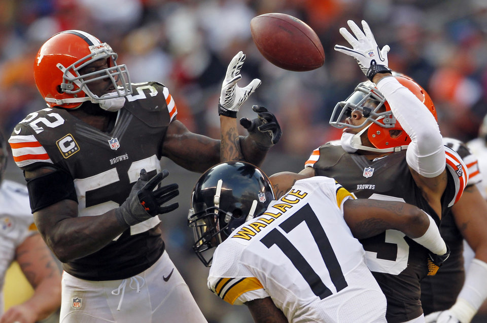 Cleveland Browns linebacker D\'Qwell Jackson (52) and cornerback Joe Haden break up a pass to Pittsburgh Steelers wide receiver Mike Wallace (17) in the fourth quarter of an NFL football game on Sunday, Nov. 25, 2012, in Cleveland. The tipped ball was recovered by Browns defensive tackle Billy Winn. (AP Photo/Ron Schwane)