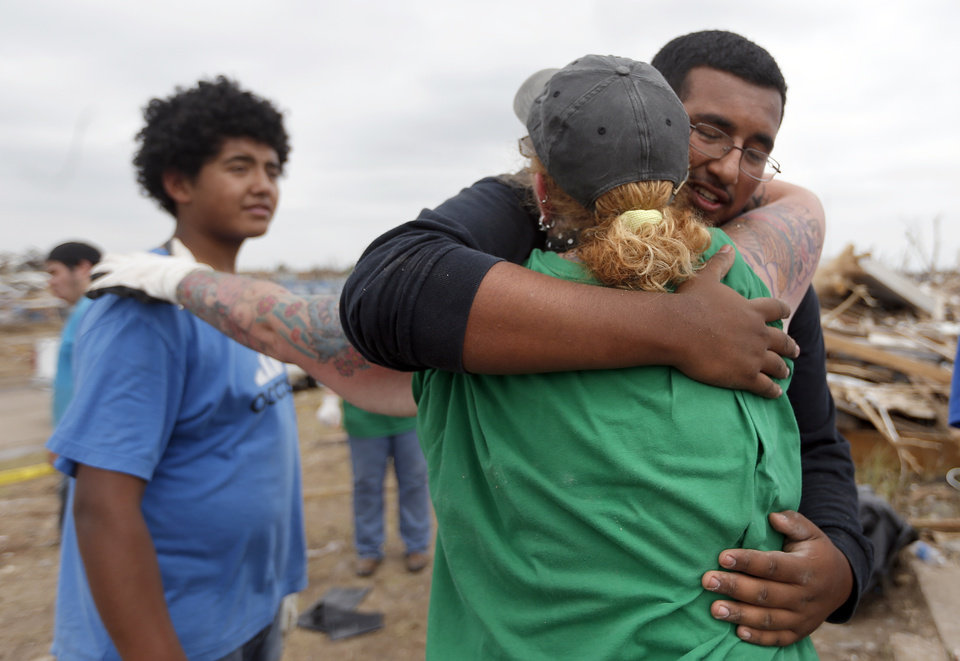 Kristy Parrish hugs Axel Gudino and Said Gudino after they found her cat Hudson Kit-ten in her destroyed home in Moore, Okla., Friday, May, 24, 2013. Photo by Sarah Phipps, The Oklahoman