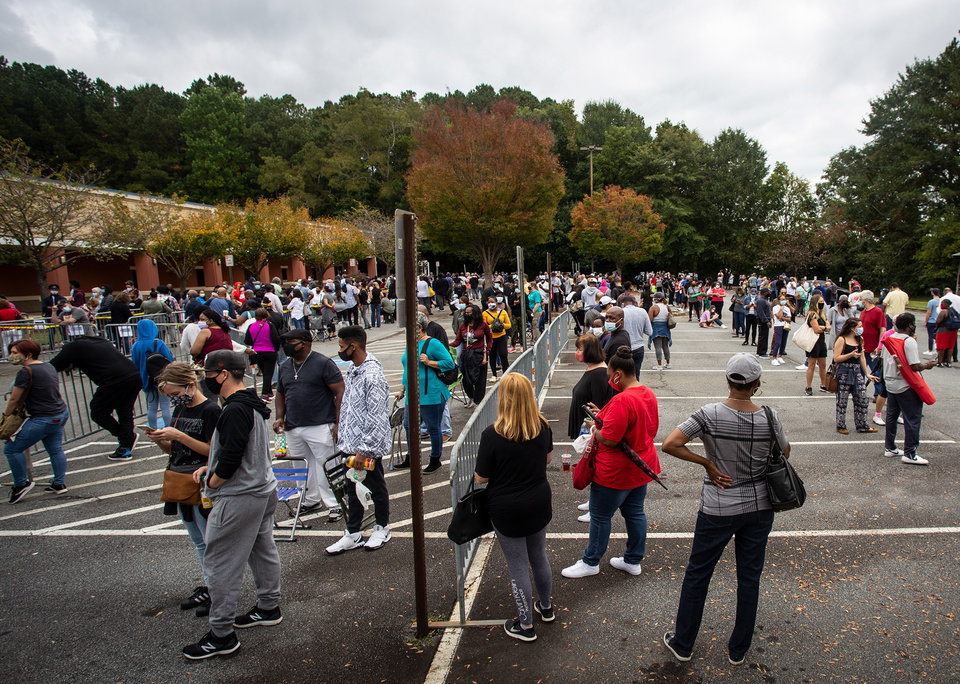 Photo -  FILE - In this Oct. 12, 2020, file photo, hundreds of people wait in line for early voting in Marietta, Ga. Black people are going to the polls by the thousands and waiting in lines for hours to vote early in Georgia. Black people are going to the polls by the thousands and waiting in lines for hours to vote early in Georgia. (AP Photo/Ron Harris, File)