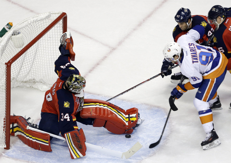 Photo - Florida Panthers goalie Tim Thomas (34) stops the puck as New York Islanders' John Tavares (91) attempts a shot on the goal during the second period of an NHL hockey game, Tuesday, Jan. 14, 2014, in Sunrise, Fla. (AP Photo/Lynne Sladky)