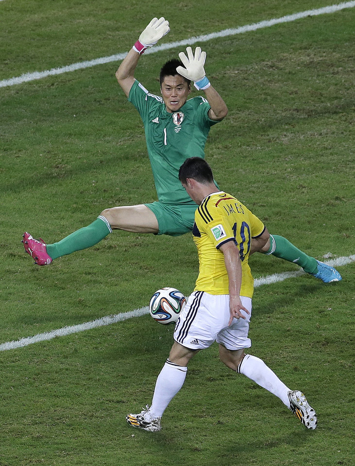 Photo - Colombia midfielder James Rodriguez, bottom, scores past Japan goalkeeper Eiji Kawashima during the second half of a group C World Cup soccer match at the Arena Pantanal in Cuiaba, Brazil, Tuesday, June 24, 2014. (AP Photo/Shuji Kajiyama)
