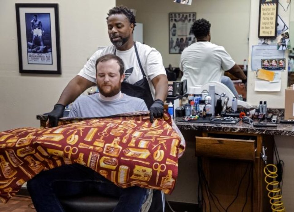 Photo -  The Oklahoman's David Dishman prepares to get a haircut and beard trim by Michael Mitchell at Versatile Styles Barber Shop at 9132 S Walker Ave. in Oklahoma City on Tuesday. [Chris Landsberger/The Oklahoman]