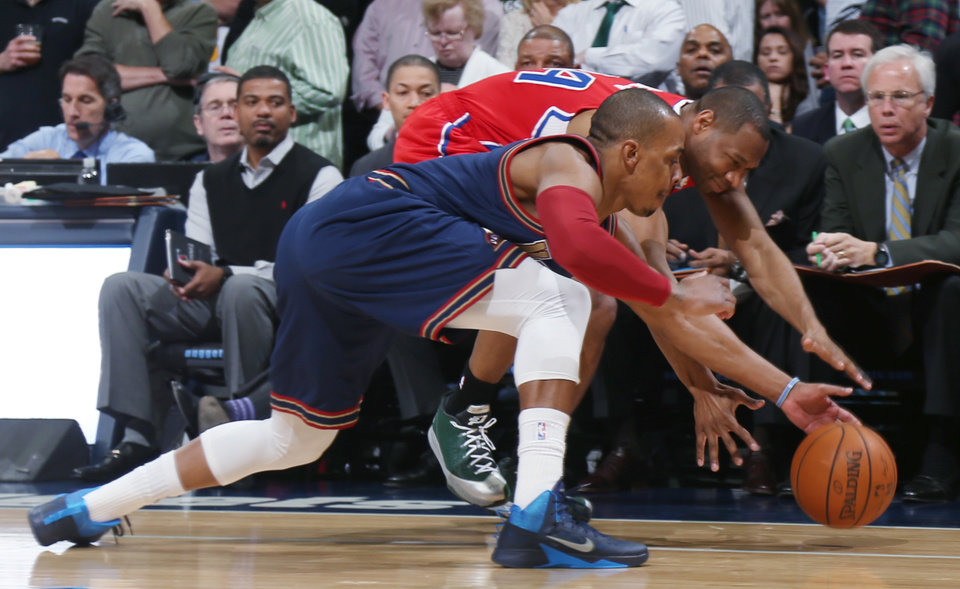 Photo - Denver Nuggets guard Randy Foye, front, pursues a loose ball with Los Angeles Clippers guard Willie Green in the first quarter of an NBA basketball game in Denver on Monday, March 17, 2014. (AP Photo/David Zalubowski)