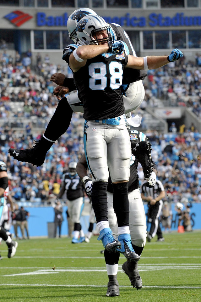 Photo - Carolina Panthers' Greg Olsen (88) and Cam Newton (1) celebrate Olsen's touchdown catch against the Atlanta Falcons during the first half of an NFL football game in Charlotte, N.C., Sunday, Dec. 9, 2012. (AP Photo/Rainier Ehrhardt)