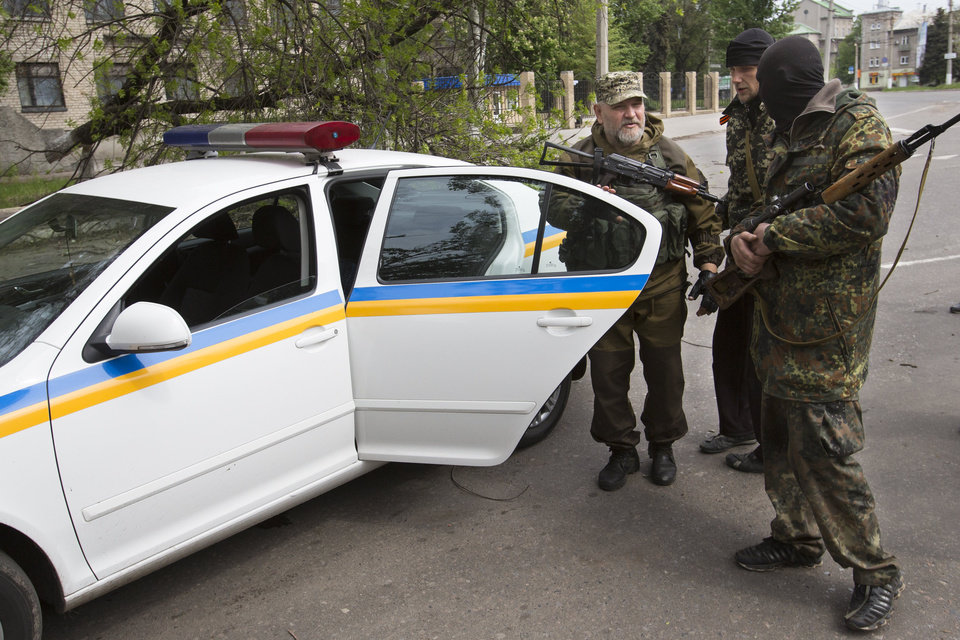 Photo - Pro-Russian gunmen listens to their commander, left, at a police car behind barricades in Slovyansk, eastern Ukraine, Friday, May 2, 2014. Ukraine launched what appeared to be its first major assault against pro-Russian forces who have seized government buildings in the country's east, with fighting breaking out Friday in a city that has become the focus of the insurgency. (AP Photo/Alexander Zemlianichenko)