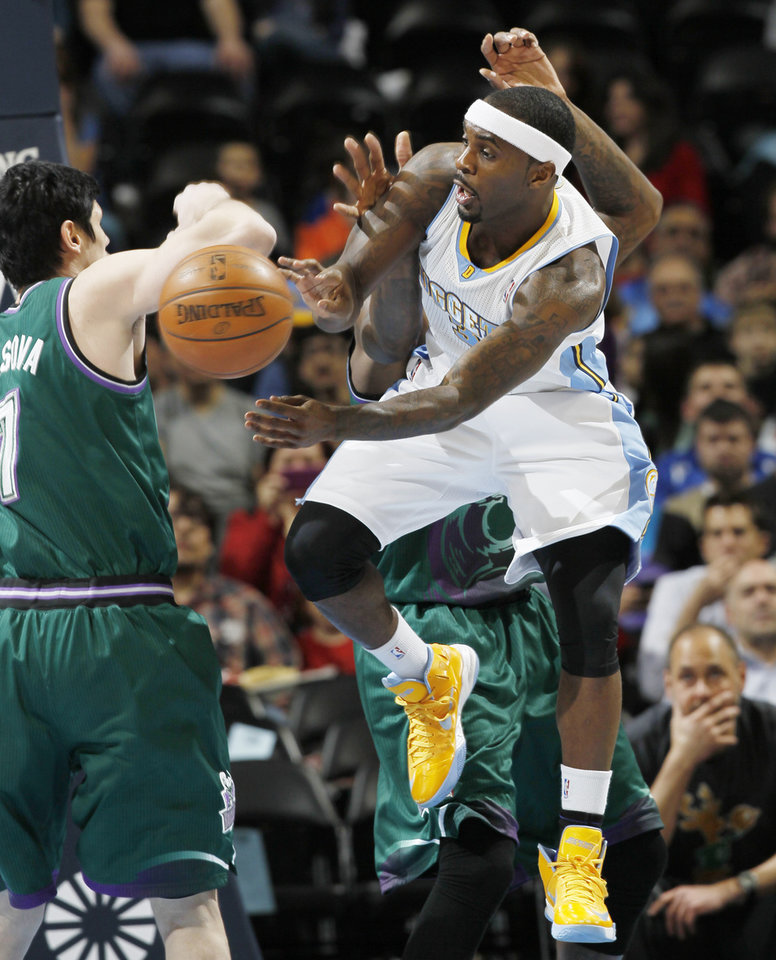 Photo - Denver Nuggets guard Ty Lawson, front, loses control of the ball as he tries to drive the lane past Milwaukee Bucks forward Ersan Ilyasova, left, of Turkey, and center Larry Sanders in the first quarter of an NBA basketball game in Denver on Tuesday, Feb. 5, 2013. (AP Photo/David Zalubowski)