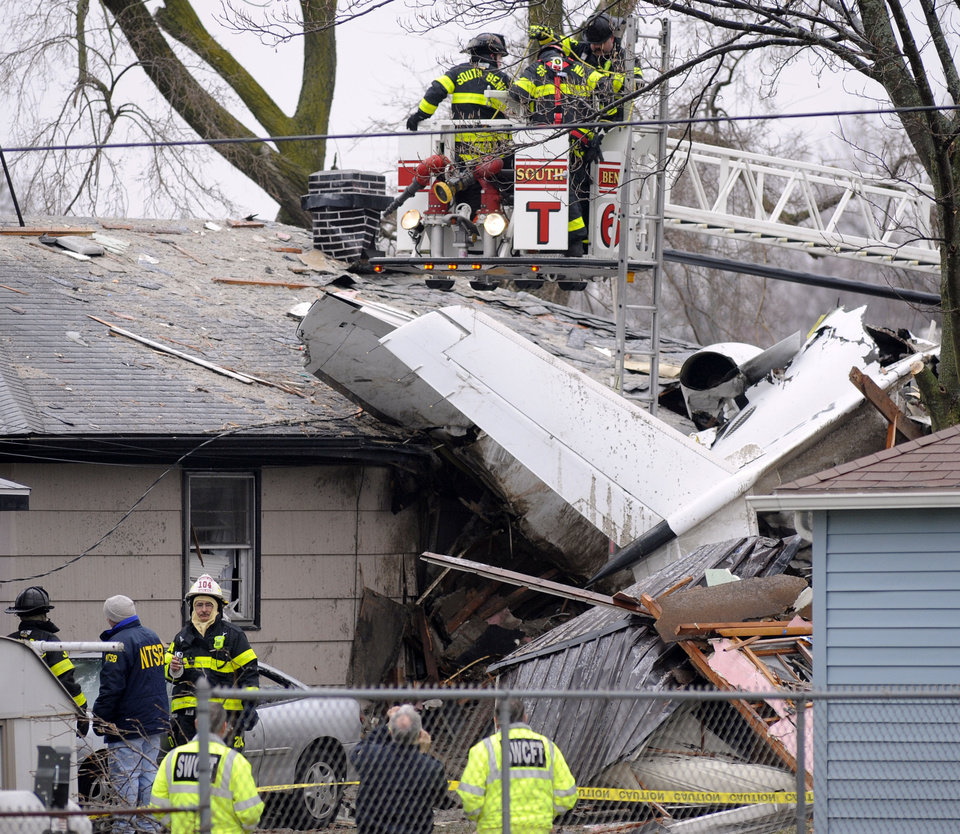 South Bend firefighters work a home, Monday, March 18, 2013, in South Bend, Ind., where a plane crashed Sunday. The plane damaged homes, as well as caused injuries, including at least two fatalities. (AP Photo/Joe Raymond) ORG XMIT: INJR105