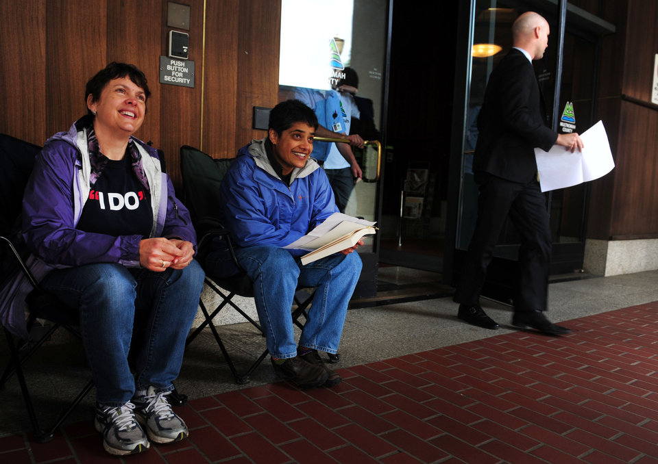 Photo - Laurel Gregory, left, and Shilpi Benerjee pass the time in front of the Multnomah County Recorder's building in Portland, Ore. on Monday, May. 19, 2014. The two are awaiting a ruling in the Marriage Equality case, so they can go into the building and get their marriage licenses. A ruling in that case is expected on Monday. (AP Photo/Steve Dykes)